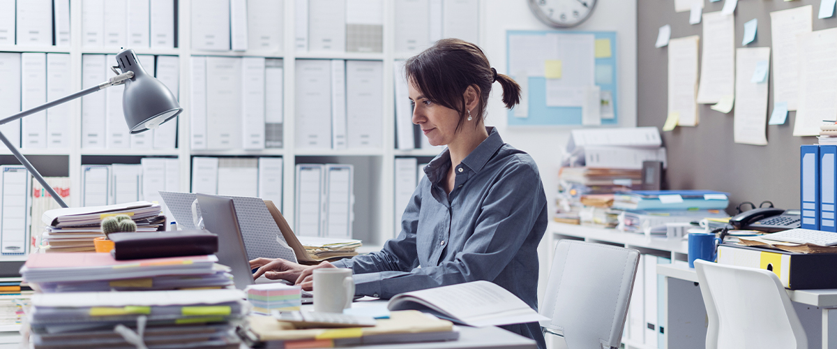 woman working on computer surrounded by files